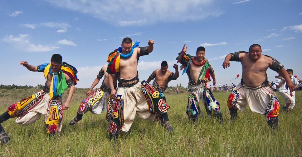 那达慕是蒙古人在风调雨顺季节举行的盛大庆典活动。那达慕上要举行传统的好汉二艺比赛。即摔跤、射箭和赛马三项。如今随着时代的变迁,射箭服饰基本没有了特别的款式。赛马服饰和摔跤服饰由于它的比赛性质,至今还或多或少地保留了一此特点,其中,奇特而华丽的当数蒙古摔跤手服饰。摔跤手服饰是把民族服饰和节目服饰合二为一的体育装束。 蒙古族摔跤服饰分内蒙古、外蒙古、西部蒙古二种类型。解放以后,内蒙古摔跤服饰,保留了传统特点的同时,吸收各地特点,逐渐形成了较为规范的基本款式。 摔跤手服饰由将军帽、罩达格(汉译为摔跤坎肩